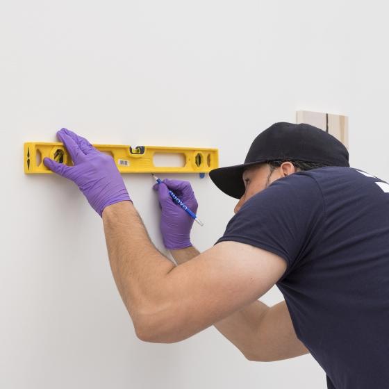 An UOVO art handler measuring wall space