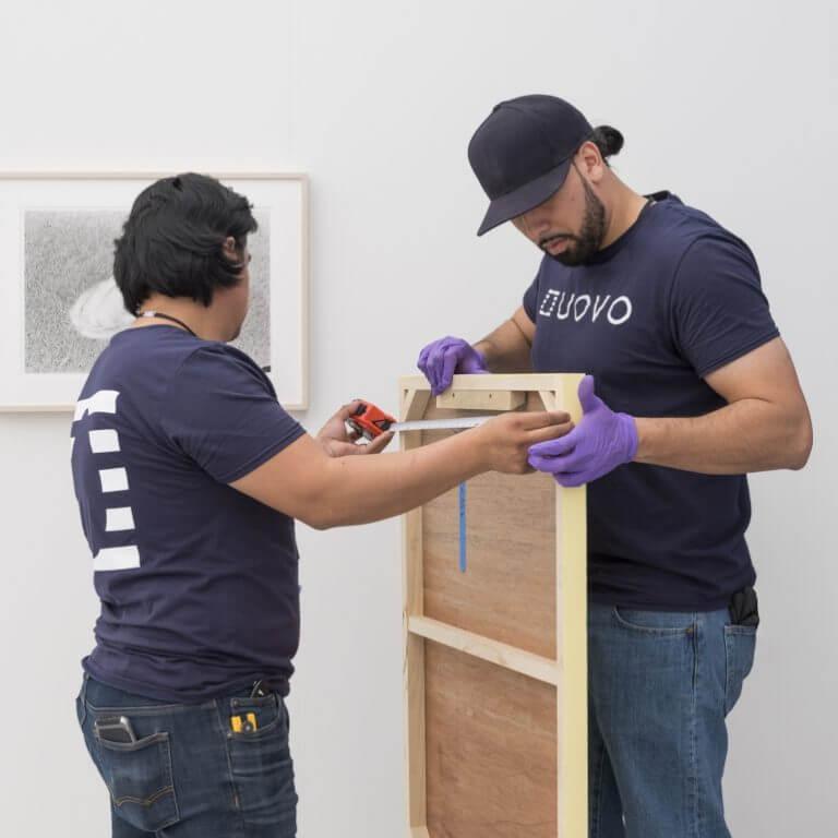 UOVO Art Handlers Installing Painting